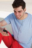 Portrait of a happy young man listening to music on his mobile phone Royalty Free Stock Photography