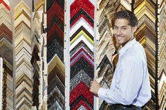 Portrait of a happy young man with multi colored frames in background Royalty Free Stock Photos