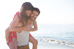 Portrait of happy young man piggybacking his girlfriend at beach. On sunny day Royalty Free Stock Images