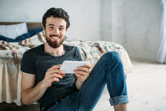 Portrait of a happy young man relaxing and watching a TV show on a tablet computer Stock Photo