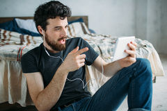 Portrait of a happy young man relaxing and watching a TV show on a tablet computer. Portrait of a young man relaxing and watching a TV show on a tablet computer Stock Photos