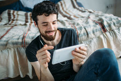 Portrait of a happy young man relaxing and watching a TV show on a tablet computer. Smiling guy pointing at the screen. He is satasfied with the video. Close royalty free stock photos