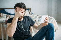 Portrait of a happy young man relaxing and watching a TV show on a tablet computer. Tricky guy closing his face with a hand but peeping through his fingers Stock Photo