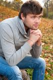 Portrait of happy young man sitting in autumn park Royalty Free Stock Photography