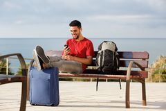 Happy young man sitting on bench with luggage and listening to music with mobile phone and earphones. Portrait of happy young man sitting on bench with luggage Royalty Free Stock Image