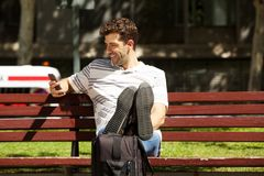 Happy young man sitting on bench outdoors with travel bag and mobile phone. Portrait of happy young man sitting on bench outdoors with travel bag and mobile Stock Images