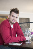 Portrait of happy young man sitting at cafe table Royalty Free Stock Photography