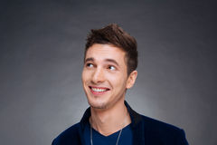Portrait of a happy young man smiling on gray background Stock Photos