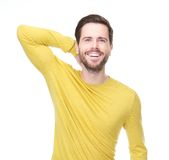 Portrait of a happy young man smiling with hand in hair Stock Photos