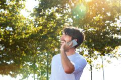 Happy young man talking on mobile phone outdoors royalty free stock photo