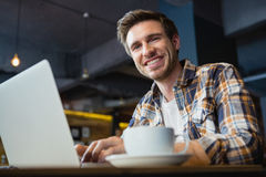 Portrait of happy young man using laptop while having coffee Royalty Free Stock Photography