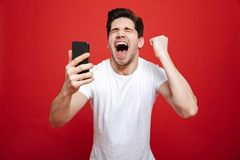 Portrait of a happy young man in white t-shirt. Holding mobile phone and celebrating over red background stock images