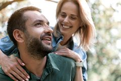 Joyful couple relaxing in forest. Portrait of happy young men enjoying nature with his girlfriend. He is carrying her on shoulders and smiling. Woman is looking Royalty Free Stock Image