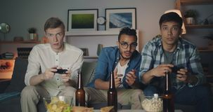 Portrait of happy men playing video game at home at night looking at camera. Portrait of happy young men playing video game at home at night sitting on sofa stock footage