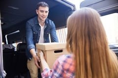 Smiling Young Man Loading Moving Van. Portrait of happy young men taking cardboard boxes from his wife and loading them into moving van Stock Photography