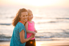 Portrait of happy young mother and daughter on beach at sunset Stock Images