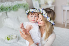 Portrait of happy young mother with her little baby in a bedroom Stock Photography