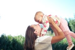 Portrait of a happy young mother lifting cute baby outdoors Royalty Free Stock Photo
