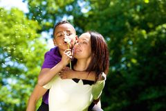Portrait of a happy young mother with son. Close up portrait of a happy young mother with son piggybacking and blowing dandelion Royalty Free Stock Image