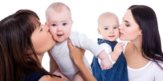 Portrait of happy young mothers kissing little daughters isolated on white. Background stock image