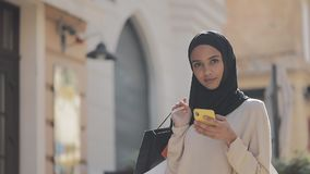 Portrait of happy young muslim woman in hijab standing with smartphone down the street with shopping bags in her hand stock video