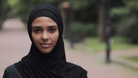 Portrait of Happy Young Musline Girl Wearing Hijab Smiling and Standing in Park Close Up. stock video footage