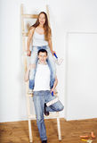 Portrait of happy young new family doing repair in own flat, couple near ladder, lifestyle people concept Royalty Free Stock Photography