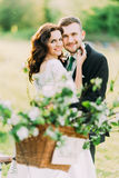 Portrait of happy young newlywed couple in park with blurred floral decor at foreground Stock Image