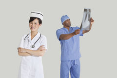 Portrait of happy young nurse with male surgeon examining x-ray report over gray background Royalty Free Stock Photography