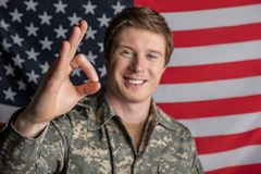 Glad male soldier working in military service. Portrait of happy young officer looking at camera and smiling. Focus on his hand showing that everything is fine Royalty Free Stock Photo