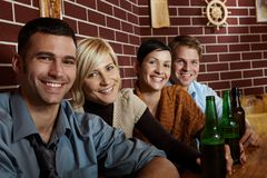 Portrait of happy young people in pub. Portrait of happy young people sitting in pub, drinking beer, looking at camera, smiling Royalty Free Stock Photography