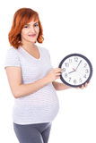 Portrait of happy young pretty pregnant woman with office clock Royalty Free Stock Images