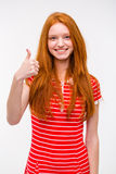 Portrait of happy young redhead woman with thumbs up gesture. Portrait of happy positive smiling attractive young redhead woman in red striped dress with thumbs royalty free stock photography