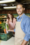 Portrait of a happy young sales clerk holding vegetables with woman in background. Portrait of a happy young sales clerk holding vegetables with women in Stock Photo