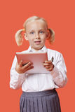Portrait of a happy young schoolgirl holding tablet PC over orange background Royalty Free Stock Images
