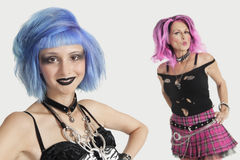 Portrait of happy young and senior female punks against gray background Royalty Free Stock Images