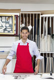 Portrait of a happy young skilled worker standing with meter stick in workshop Stock Photography