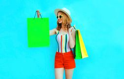 Portrait happy young smiling woman holding shopping bags in colorful t-shirt, summer round hat on blue wall royalty free stock image