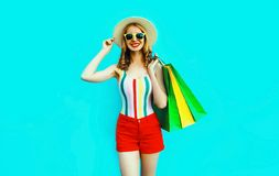 Portrait happy young smiling woman with shopping bags in colorful t-shirt, summer round hat on blue wall. Background royalty free stock photo