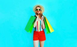 Portrait happy young smiling woman with shopping bags in colorful t-shirt, summer round hat, red shorts on blue wall. Background royalty free stock images