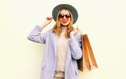 Portrait happy young smiling woman with shopping bags in pink coat, round hat on wall. Background stock photography