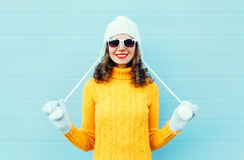 Portrait happy young smiling woman wearing a sunglasses, knitted hat, sweater over blue. Background Royalty Free Stock Photos