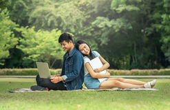 Portrait of a happy young students sitting on the park and using laptop stock photos