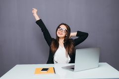 Portrait of happy young successful businesswoman celebrate something with arms up. Happy woman sit at office and look at laptop. P Royalty Free Stock Photo