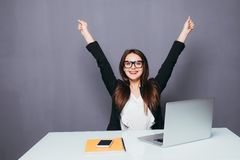 Portrait of happy young successful businesswoman celebrate something with arms up. Happy woman sit at office and look at laptop. P stock image