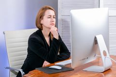 Portrait of happy young successful businesswoman at office. She sits at the table and carefully looks at the display. Black Friday. Or Cyber Monday. Selecting royalty free stock images