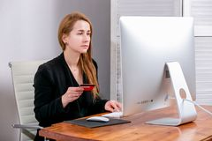 Portrait of happy young successful businesswoman at office. She sits at the table and enters credit card details on the keyboard. stock photos