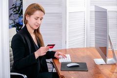 Portrait of happy young successful businesswoman at office. She sits at the table and enters credit card details on the keyboard. royalty free stock photography