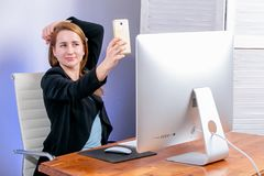 Portrait of happy young successful businesswoman at office. She sits at the table and makes selfies. Black Friday or Cyber Monday. stock photos