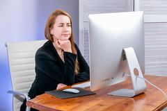 Portrait of happy young successful businesswoman at office. She sits at the table and sadly looks at the display. Black Friday or. Cyber Monday. Selecting items royalty free stock photography